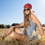 Hippie girl sitting on a meadow - morning outdoors shot Stock Photos
