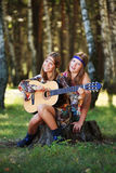 Hippie girls with guitar on nature Stock Photos