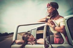 Hippie girls on a road trip. Hippie girls in a minivan on a road trip stock photo