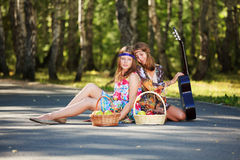 Hippie girls sitting on the road Royalty Free Stock Image