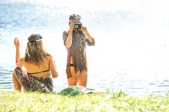 Hippie girls taking photos with an old camera and smoking - Vint. Pretty free hippie girls on the grass taking photos with an old camera and smoking. Outdoor in Stock Image