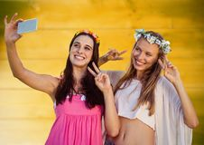 Hippie girls taking selfie against blurry yellow wood panel Royalty Free Stock Images