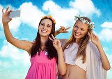 Hippie girls taking selfie against cloudy sky Stock Photo