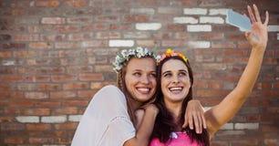Hippie girls taking selfie against red brick wall Stock Image