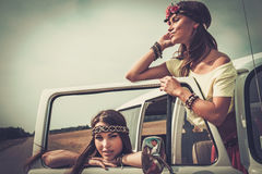 Hippie girls in a van on a road trip.  Stock Images