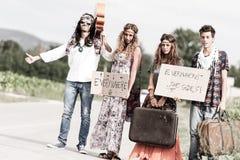 Hippie-Gruppe, die auf einer Landschafts-Straße per Anhalter fährt stockfotos
