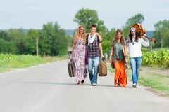Hippie-Gruppe, die auf einer Landschafts-Straße per Anhalter fährt lizenzfreie stockfotos