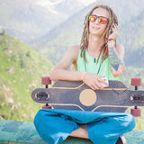 Hippie handsome man with skateboard and mobilephone listening to music Stock Image
