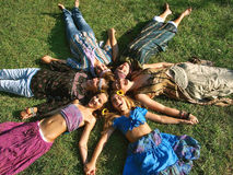 Hippie heads. A group of young hippie women (best friends - sisters) lying on the grass and their heads and hands together in circular formation. Horizontal royalty free stock photography