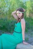 Hippie hermoso de la muchacha en un vestido verde que se sienta en un registro Imágenes de archivo libres de regalías