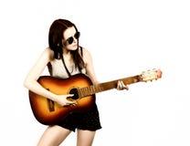 Hippie hermoso joven que toca la guitarra en fondo ligero Foto de archivo
