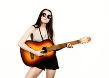 Hippie hermoso joven que toca la guitarra en fondo ligero Fotografía de archivo