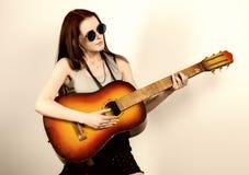 Hippie hermoso joven que toca la guitarra en fondo ligero Imagen de archivo libre de regalías