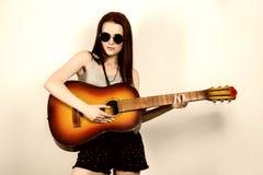 Hippie hermoso joven que toca la guitarra en fondo ligero Imagen de archivo