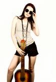 Hippie hermoso joven que toca la guitarra en fondo ligero Foto de archivo libre de regalías