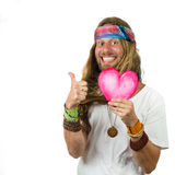 Hippie holding a love heart gestering thumbs up. Funny, very happy hippie colorful man holding a love heart gesturing thumbs up isolated on white Stock Photography