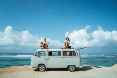 Hippie-Junge, der Gitarre mit Freundin auf Retrostil spielt lizenzfreies stockfoto