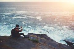 Hippie-Kerl, der Fotos der erstaunlichen Landschaft auf mobiler intelligenter Telefondigitalkamera beim Sitzen auf einem Felsen n Lizenzfreies Stockbild