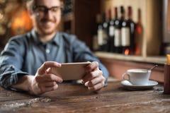 Hippie-Kerl im Restaurant unter Verwendung eines Handys stockfotografie