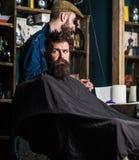 Hippie-Kunde, der Haarschnitt erhält Haarschnittprozeßkonzept Mann mit dem Bart bedeckt mit dem schwarzen wartenden Kap während F Lizenzfreies Stockbild