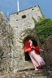 Hippie lady descending a staircase at a ruined English castle on a windy day royalty free stock photo