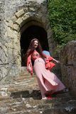 A happy hippie lady on steps near an English castle`s ancient doorway stock image