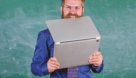 Hippie-Lehrerabnutzungsbrillen und Krawattenbisslaptop Mann hungrig für Wissen Er benötigt neue Informationen Durst von lizenzfreie stockfotografie
