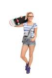 Hippie-Mädchen, das ein Skateboard über ihrer Schulter trägt Lizenzfreie Stockfotos