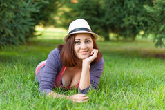 Hippie-Mädchen, das im grünen Gras liegt Stockbild
