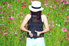 Hippie-Mädchen, das Kamera und Stellung Nikon DSLR unter in Kosmosblumengarten hält Lizenzfreies Stockbild