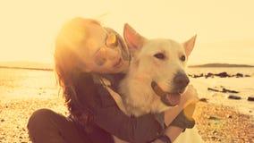 Hippie-Mädchen, das mit Hund an einem Strand während des Sonnenuntergangs spielt Stockfotografie