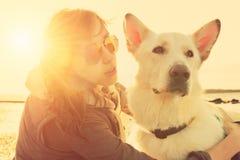 Hippie-Mädchen, das mit Hund an einem Strand während des Sonnenuntergangs, starker Blendenfleckeffekt spielt Lizenzfreies Stockbild