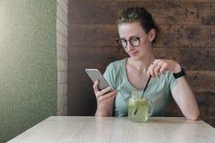 Hippie-Mädchen in den Gläsern sitzt im Café bei Tisch, trinkt Getränk und benutzt Smartphone Geschäftsfraufunktion, blogging Lizenzfreie Stockfotografie