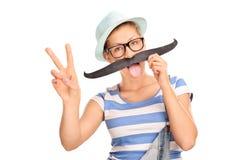 Hippie-Mädchen mit dem gefälschten Schnurrbart, der ein Friedenszeichen macht Lizenzfreies Stockfoto