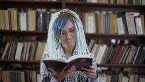Hippie-Mädchen mit den Dreadlocks absorbiert im Lesebuch in der Bibliothek stock video