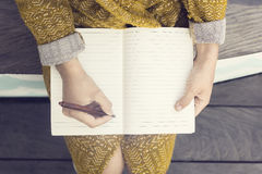 Hippie-Mädchen mit leerem Tagebuch und Stift, der auf Holzbank sitzt Stockfotos