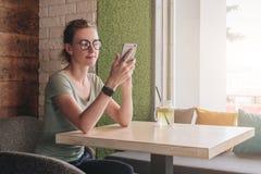 Hippie-Mädchen sitzt im Café bei Tisch nahe Fenster und überprüft E-Mail auf Smartphone Student, der, blogging lernt Lizenzfreie Stockfotos
