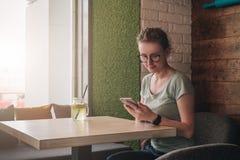 Hippie-Mädchen sitzt im Café bei Tisch nahe Fenster und schaut auf Schirm von Smartphone Junge Geschäftsfraufunktion Stockbilder