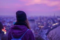 Hippie-Mädchenreisender, der Winterabendstadtbild, purpurroten violetten Himmel und Stadtlichter betrachtet Lizenzfreies Stockfoto