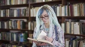 Hippie-M?dchen absorbiert im Lesebuch in der Bibliothek stock footage