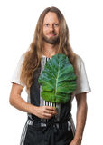 Hippie man holding a kale leaf over his heart. Handsome hippie man holding a kale leaf over his heart as a concept for good health. Isolated on white royalty free stock photos