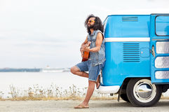 Hippie man playing guitar over minivan on beach. Nature, summer, youth culture, music and people concept - young hippie man playing guitar and singing over Royalty Free Stock Images