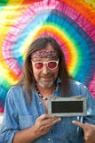 Hippie man pointing towards a blank blackboard. Funny hippie middle-aged man wearing blue denim shirt, headband, necklace and red sunglasses, while smiling and Stock Photos