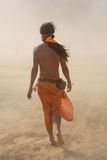 Hippie man walking in a sand storm dressed with orange fabrics Stock Photo