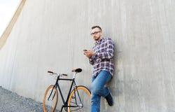 Hippie-Mann in den Kopfhörern mit Smartphone und Fahrrad Stockfoto