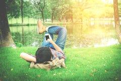 Hippie-Mann, der auf dem Gras unter Verwendung des intelligenten Telefons sich entspannt Stockbild