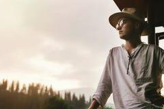 Hippie-Mann, der auf dem Portal des Holzhauses mounta betrachtend steht Lizenzfreie Stockfotografie