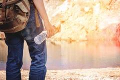 Hippie-Mann, der Flasche Wasser in Sommerfluß hält Stockfoto