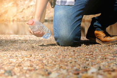 Hippie-Mann, der Flasche Wasser in Sommerfluß hält Stockfotografie