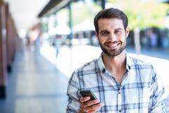 Hippie-Mann, der seinen Smartphone in der Stadt verwendet lizenzfreies stockfoto